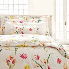 A gorgeous floral duvet cover in vivid fuchsia pink, lemon yellow, orange, with touches of green and turquoise.  This lively watercolor print looks wonderful paired with all white or with bright and colorful solid coordinates.