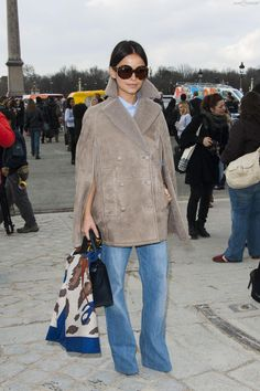 Miroslava Duma looks chic in a cape coat and wide leg jeans. #PFW