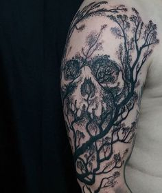 Skull themed sleeve tattoo design. Inked in black, the skull is formed through the help of tree branches and tree leaves in silhouette.