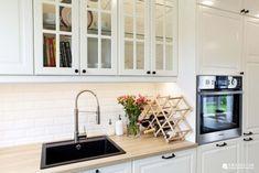 Białe szafki w tradycyjnej formie podkreślają szczególny charakter kuchni. Podświetlenia w witrynkach oraz lampki nad blatem pełnią funkcję praktyczną, a także subtelnie dekorują wnętrze.