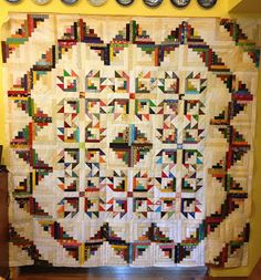 Lucy's Quilts: 4 central Log Cabin blocks and 8 Bear's Paw variations surrounded by Log Cabins.