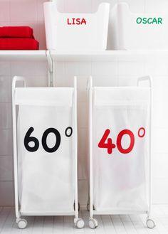 2 hvide IKEA vasketøjskurve med hjul. Der er klistermærker med forskellige temperaturer på kurvene.