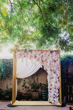 Gold frame backdrop with white fabric on one side and pink flowers