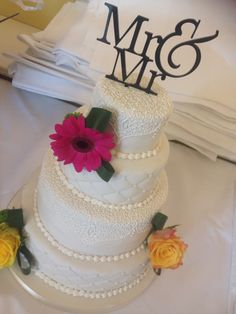 Stunning Ivory four tiered wedding cake wither royal icing  lace effect and quilt effect with fresh summer flowers