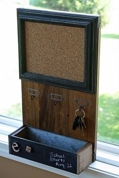 love this...old board with cork glued on and an old frame on top; cup hooks; skinny old drawer... wow!
