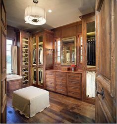 His closet with wood floors and built-in cabinetry resembles a fine men's shop.  Love the antique entry door!