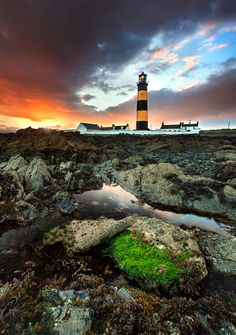 (St Johns Point Lighthouse in County Down, Northern Ireland is an impressive lighthouse by any standards. Surrounded by the jagged rocks on the coast, the Mourne mountains make the perfect backdrop.)