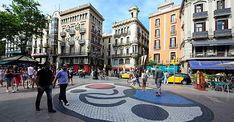 """The Rambla, often plural """"Las Ramblas"""".The approximately 1.3 km long road - in the middle a pedestrian zone - is ranging from Plaça Catalunya, probably the central transport hub in Barcelona to the port. The Rambla del Mar is an extension of the historic Ramblas to the Maremagnum, a shopping centre in the harbor - Barcelona"""