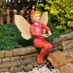 """Scarlet Pimpernel Fairy by Fairies. $14.99. size: 4"""" High. material: Resin. What pleasure the Scarlet Pimpernel Fairy finds sitting in the garden and listening to the adventures of other fairies. Many events have been woven into the storytales of the fairies, describing Pimpernel's fulfillment of destiny in the mini-garden."""