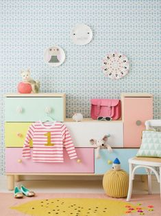 chambre rose et gris, murs en bleu pastel et blanc, tapis en rose et jaune, meubles avec des grands tiroirs casiers en jaune, bleu pastel et rose bonbon, trois plats décoratifs en rose, blanc et bleu suspendus au mur