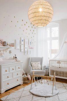 Une chambre bébé avec un tapis berbère et une suspension en rotin