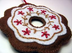 This felt ornament looks like a frosted gingerbread cookie. Love the pop of red on the white.