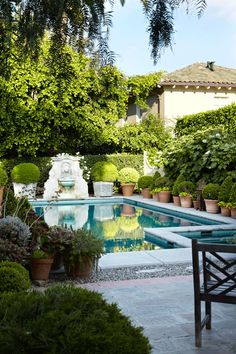 A lovely Tuscan-style fountain brings classic beauty to this backyard pool and lounge area. Potted plants and shrubs line the pool to enhance the lush, natural environment.