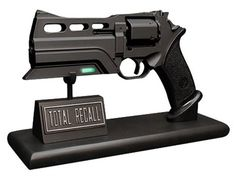 """Total Recall 10"""" Blaster Prop Replica. Available: 02/27/13.To celebrate the theatrical release of the new SciFi Blockbuster movie Total Recall, we are pleased to present our prop replica of the hero blaster used extensively throughout the movie. This replica was molded directly from a screen used blaster to ensure complete accuracy. Comes complete with a green light-up LED under the barrel - like the original! Constructed from heavyweight poly stone, then hand painted to detail. Price: $199.99"""