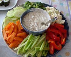 Dip de queso crema y hierbas frescas (2 cucharadas de aceite de oliva, 1 queso crema de 250 gr, ½ taza de perejil fresco, ½ taza de albahaca picada, ½ taza de queso parmesano, 3 cucharadas de yogur, Sal y pimienta al gusto) Para acompañar • Palitos de zanahoria • Palitos de apio • Florecitas de brócoli • Florecitas de coliflor • 1 pimentón rojo y un pimentón verde cortados en tiritas • Tiras de pepino