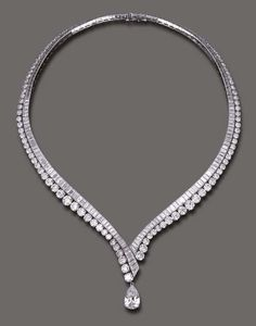 AN ELEGANT DIAMOND NECKLACE, BY VAN CLEEF & ARPELS The flexible V-shaped baguette-cut diamond line, enhanced by graduated circular-cut diamond trim, the front suspending a detachable pear-shaped diamond, weighing approximately 4.11 carats, mounted in platinum and 18k gold