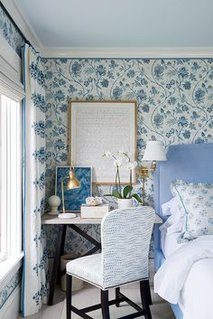 Coastal Living 2017 Idea House | Lighter blue hues were introduced in the master bedroom, accented by warm brass lighting and framed art. The Enrico Table Lamp by Thomas O'Brien provides task light at the desk. A pair of Triple Swing Arm Wall Lamps by Studio VC flank the bed for evening reading. #circalighting