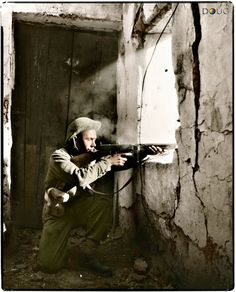An Allied soldier firing his Thompson from a house in Cupa, near the Gariglaino River in Italy. 15th November 1943. (Colourised by Doug)
