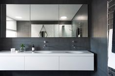 The counter and sink combination were made specifically for this bathroom from a single piece of Solid Surface material, with two sink bowls slumped out of the top surface.