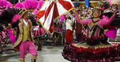 Mestre-sala e porta-bandeira desfilam de preto e rosa