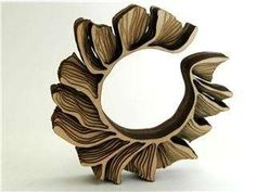 """""""UK artist Anthony Roussel combines 3-D software and high tech laser cutting techniques to transform the traditional material of wood into these original bracelets. The resulting jewelry is modern in its design, with a flash of inspiration from topographical maps. The darkening of the edges is a consequence from the laser burning its way through the wood, adding to the three dimensional effect."""""""