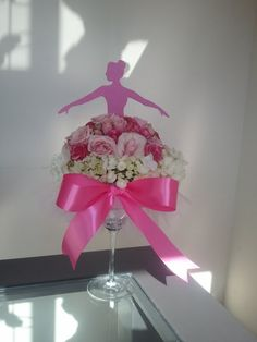Ballerina centerpiece - made with a margarita glass, floral foam, hydrangea, roses, and topped with a ballerina silhouette. Also has tulle and ribbon wrapped around the glass.