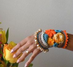 This cuff is crocheted in orange, cocoa, khaki, yellow and turquoise... accented with coconut and wooden beads.. Romantic, Bohemian, great for