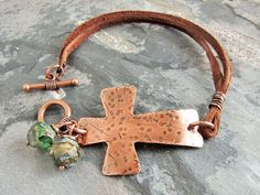A fun copper cross bracelet with a rustic boho vibe.  ► hand sawn from 22 gauge copper ► cross measures 2 long ► hammered texture for a distressed look ► double strand brown leather cord ► Czech glass nuggets in green/caramel/brown mix ► toggle clasp ► oxidized patina and tumble polished ► sealed with a protective coating  SIZING: For a comfortable fit, add 3/4 to your wrist size. If your purchase is a gift and you dont know the wrist size, the average bracelet length is 7. Please select the…