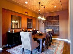 Three iron pendant lights descend from a wallpapered ceiling to play up the drama in this eclectic dining room.