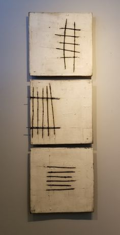 White with Wire by Lori Katz. Slab-built stoneware with slips, high-temperature wire, and underglaze. Each square is backed on wood and wired to hang simply on a picture hook. Dimensions below reflect set of three as shown. Individual squares measure 15.5