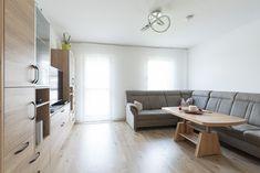 Ein helles Wohnzimmer mit passenden Möbeln zum Boden. Durch die weißen Fenster aus der HARTL HAUS Tischlerei ist der Raum mit Licht durchflutet. Table, Furniture, Home Decor, Bright Living Rooms, Carpentry, Windows, Boden, Decoration Home, Room Decor