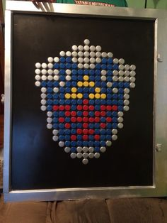 8 bit Hylian Shield for me using bottle caps and an old farm window.