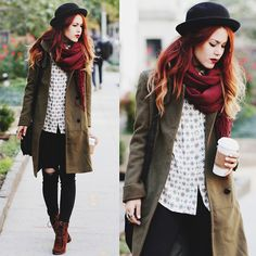 Black bowler hat, red scarf, olive coat, printed blouse, ripped black skinny jeans, brown boots.
