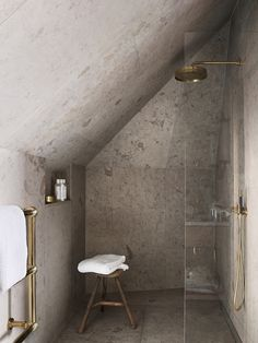 Incredible attic bathroom shower features gray stone tiled walls, floors and ceilings fitted with a brass rainfall shower head over a glass partition and adjustable brass shower head across from a tiled niche and tripod stool situated beside a brass towel rack.