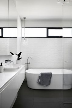 This modern and simple black and white bathroom has slightly textured white tiles, a standalone bathtub and a walk-in glass shower. #bathroomsinkhardware #bathroomdecor #bathroomdesign #bathroomdesignideas #modernbathroom