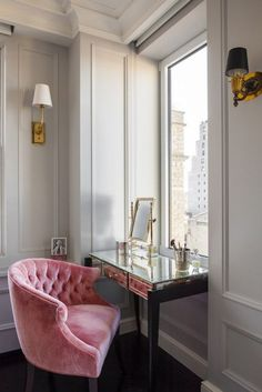 Glam dressing room features gray walls adorned with gray trim moldings frame window situated over a mirrored make up vanity paired with pink velvet tufted vanity chair with barrel back illuminated by a Thomas O'Brien Hulton Sconce in Hand Rubbed Antique Brass.