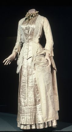Wedding dress Date: 1882 Media: Satin, Moire Silk, And Lace Country: France Accession Number: 53820.1a Ivory satin cuirasse-style bodice with pleated front, 3/4 sleeves with lace cuffs. Pleated flounce at hemline. Elaborately trimmed with fine lace applique. Polonaise style skirt with bustle, no train.
