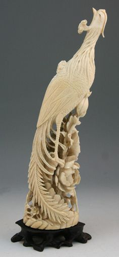 Chinese finely carved ivory phoenix: perching on branch above large peony blossoms with it's head up, with wood stand; Qing Dynasty
