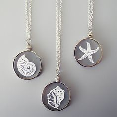 """Handcut paper pieces encased between 2 micro-thin pieces of glass. Cut by hand with an x-acto knife and ready to wear with a 24"""" silver chain. By Sarah Trumbauer on Etsy"""