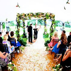 The wedding couple stand beneath a floral chuppah.