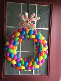 DIY dollar store Easter wreath for less than $8!!  I used a dollar store pool noodle, taped the two ends together, used a hot glue gun to attach all the eggs (about 60), and added ribbon. Takes less than an hour (unless you have two very curious toddlers).  What you need from the dollar store::  1 pool noodle 5 bags of 18 ct Easter eggs-your choice of colors 1 roll of ribbon  A total of $7!  You'll also need packing tape or duct tape and a hot glue gun. Glue eggs on in different directions…