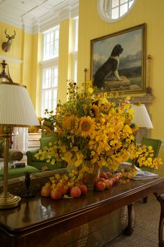 Lovely display of yellow flowers and apples in this very sunny room! Love the green chairs!