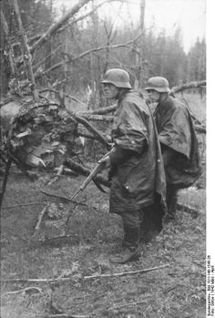 Southern Russia, spring 1942: Two German grenadiers, wearing rain capes, approach enemy positions with their rifles ready.