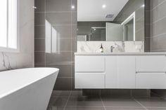 The grey tiles of this bathroom offset the imposing, trapezoidal feature bathtub.
