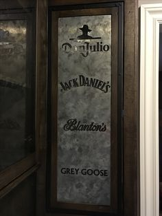 Aged zinc panel in a bar cabinet door with logo cutouts.