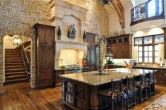 This kitchen is stunning! Love the stone wall, the arched opening to the back stair case and the gorgeous kitchen island stools with the scrolly legs. What about the lantern affixed to the island?!