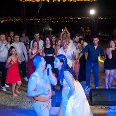 Crazy wedding party in Thessaloniki, Greece. Groom and bride singing in front of guests