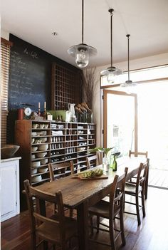 rustic dining room with wood open kitchenware cabinet shelves and chalkboard painted wall