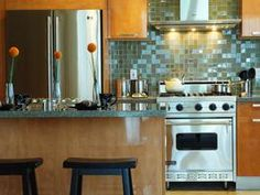 Designer Ammie Kim wanted to give this kitchen a modern look by creating a unique backsplash. The glass tiles in the backsplash alternate between glossy and etched, complementing the glossy stainless steel appliances and honey maple cabinets. Painting Kitchen Tiles, Blue Kitchen Tiles, Kitchen Backsplash, Backsplash Ideas, Blue Backsplash, Kitchen Cabinets, Tile Ideas, Wood Cabinets, Paint Backsplash