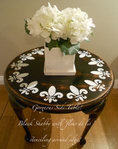 Black shabbied side table with 'fleur de lis' stencil